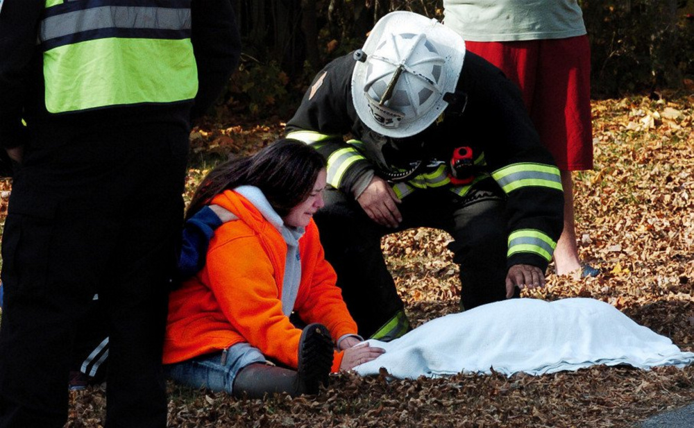 Skowhegan Fire Chief Shawn Howard comforts Danette Dalton on Nov. 2 after he carried her deceased dog out of her home on Cote Street in Skowhegan, which a fire had damaged beyond repair.