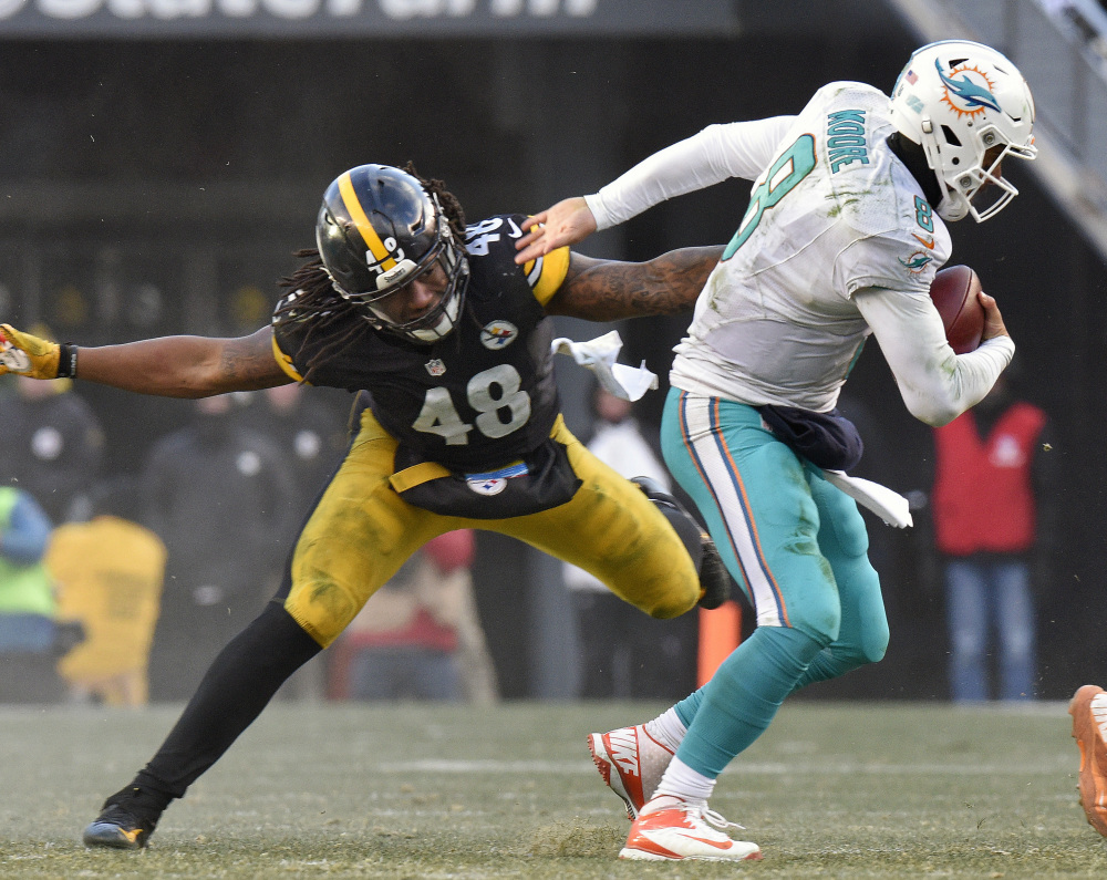 Miami Dolphins quarterback Matt Moore eludes the grasp of Pittsburgh outside linebacker Bud Dupree during the second half Sunday in Pittsburgh.