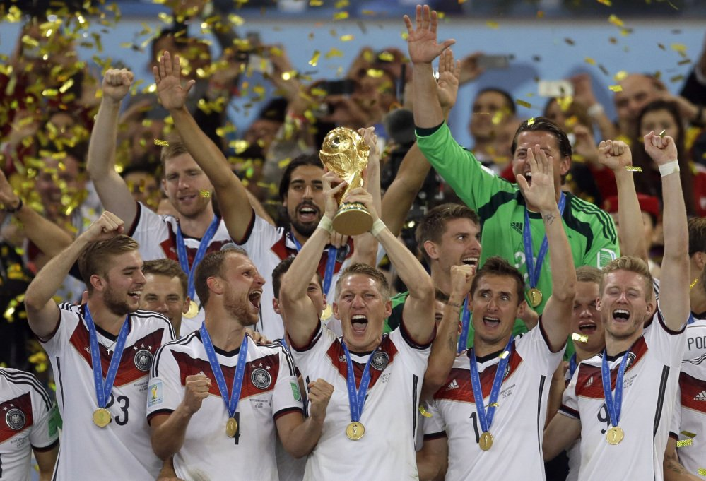 In this July 13, 2014 photo Germany's Bastian Schweinsteiger holds up the World Cup trophy as the team celebrates their 1-0 victory over Argentina after the World Cup final soccer match at the Maracana Stadium in Rio de Janeiro, Brazil. FIFA is about to make the World Cup a bigger and, it hopes, richer event even at the cost of lower quality soccer.