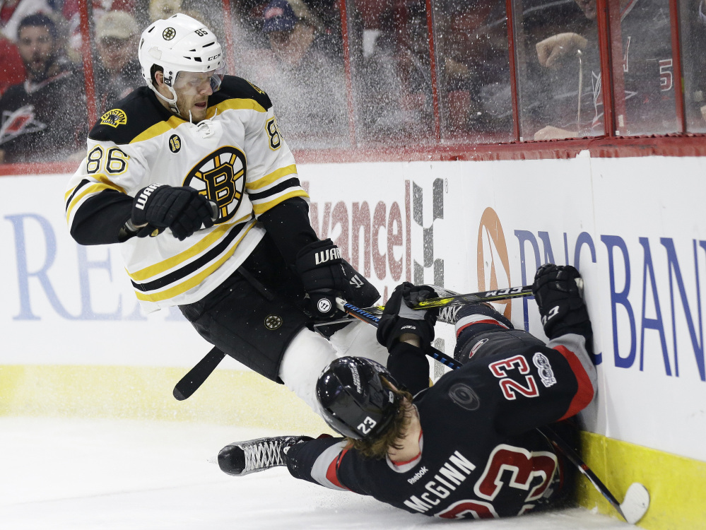 Boston Bruins' Kevan Miller (86) and Carolina's Brock McGinn collide while chasing the puck during the second period Sunday.