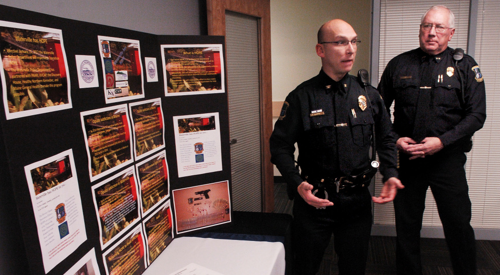 "Waterville police Deputy Chief Bill Bonney, left, and Chief Joe Massey speak beside a display of opiate drugs and statistics on the increase of drug use Nov. 16 during a news conference at which authorities announced Operation HOPE, a program that aims to help drug addicts get treatment. Volunteer ""angels"" soon will meet with program participants to help them find treatment and recover."