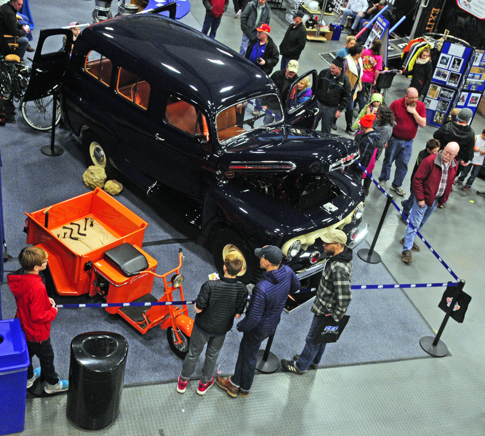 Staff photo by Joe Phelan   People look at vehicles on display in the PEP Classic Car Company booth during the Northeast Motorsports Expo on Saturday at the Augusta Civic Center.