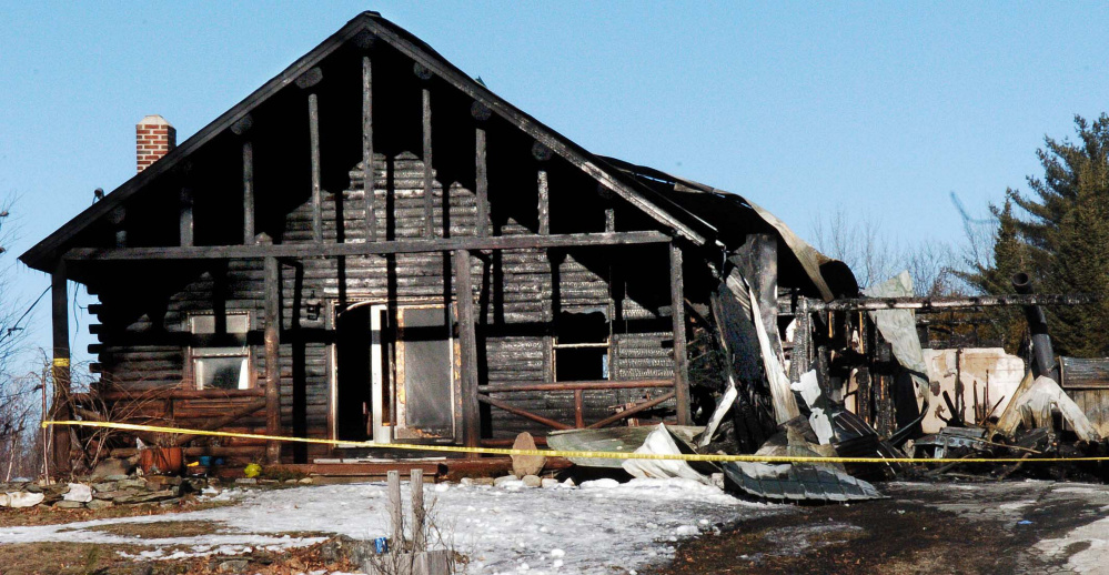 On Sunday, police tape surrounds a burned log home at 1178 China Road in Winslow that was destroyed by fire last Friday.