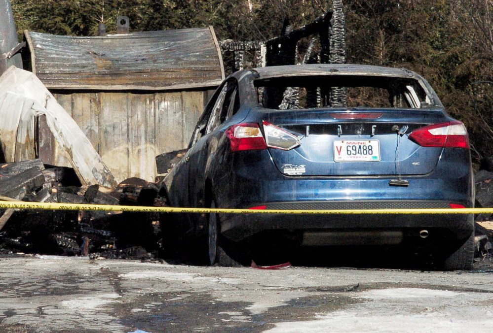 On Sunday police tape surrounds a burned garage and vehicle that were destroyed by fire along with the log home at 1178 China Road in Winslow last Friday.