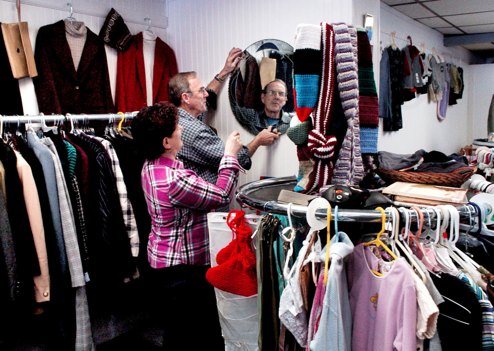 Volunteers Marsha and Sonny Lagasse hang a mirror in the clothing section at the new St. Peter's Thrift Store and Food Pantry in Bingham at the former Jimmy's Market on Main Street on Wednesday.