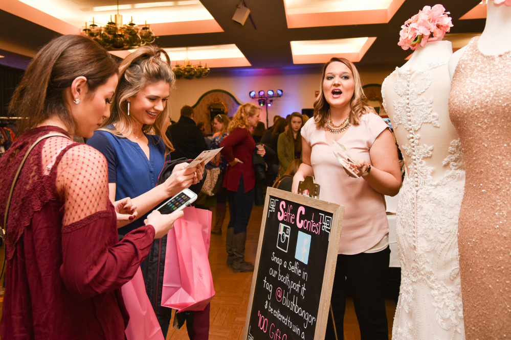 Callie LaChance, left, of Mount Vernon, and P.H. Cody, middle, of Bucksport, listen to exhibitor Karami Mantz, right, of Bangor, discuss wedding dress styles at the annual Bridal Expo at the Augusta Civic Center Sunday.
