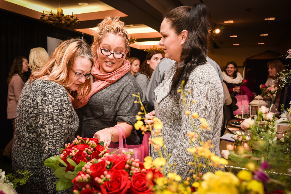 The Bridal Expo at the Augusta Civic Center attracted a large crowd. Shown here inspecting floral options are, left to right, Amber Dyer of Clinton, Rachel Lane of Benton and Ashley Ferris of Shawmut.