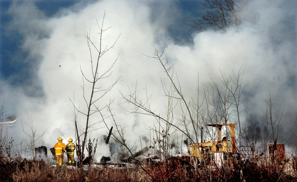 Smoke rises as firefighters put out the fire that flattened a building on the Whitten Road in Burnham on Monday.