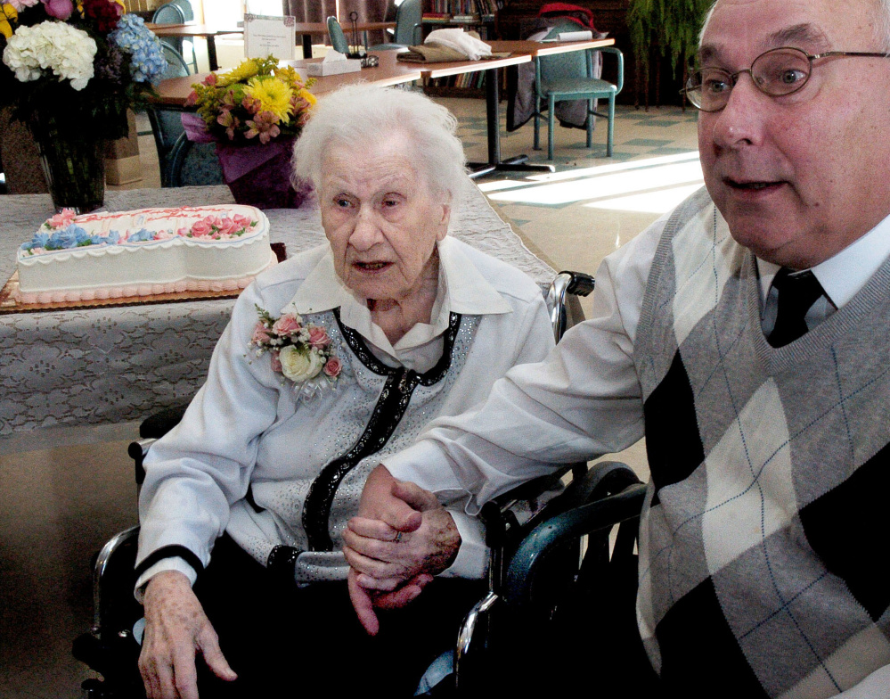 Ann Labin and her son David hold hands while talking about her long life prior to her 100th birthday party at the Maple Crest Home in Madison on Monday.