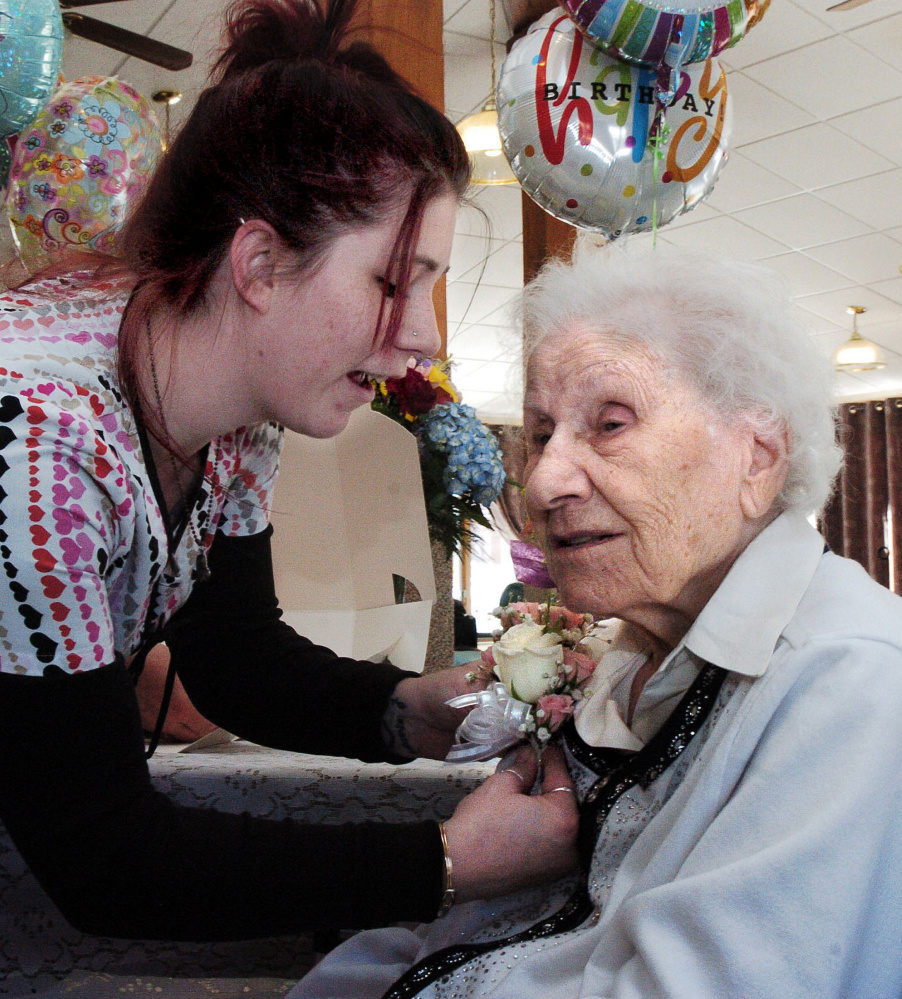 Hillary Dillingham pins a corsage on Ann Labin prior to her 100th birthday party at the Maple Crest Home in Madison on Monday.