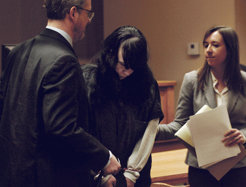 Miranda Hopkins, of Troy, is flanked Tuesday by defense attorneys in Belfast District Court after an initial appearance on a charge of murder in connection with the death of her 7-week-old son.