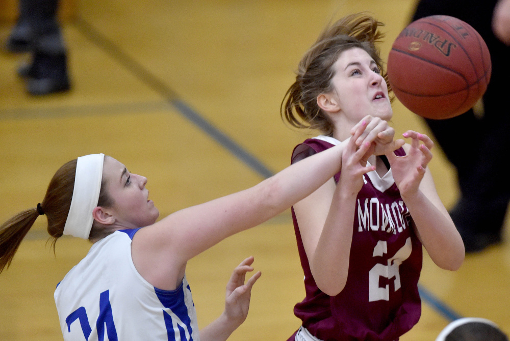 Madison junior Marah Hall, left, fouls Monmouth's Kaeti Butterfield during a Mountain Valley Conference game Tuesday night.