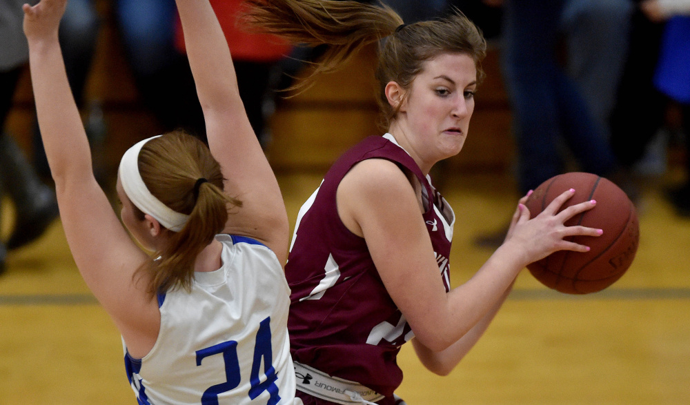 Madison junior forward Marah Hall fouls Monmouth forward Kaeti Butterfield during a Mountain Valley Conference game Tuesday night.