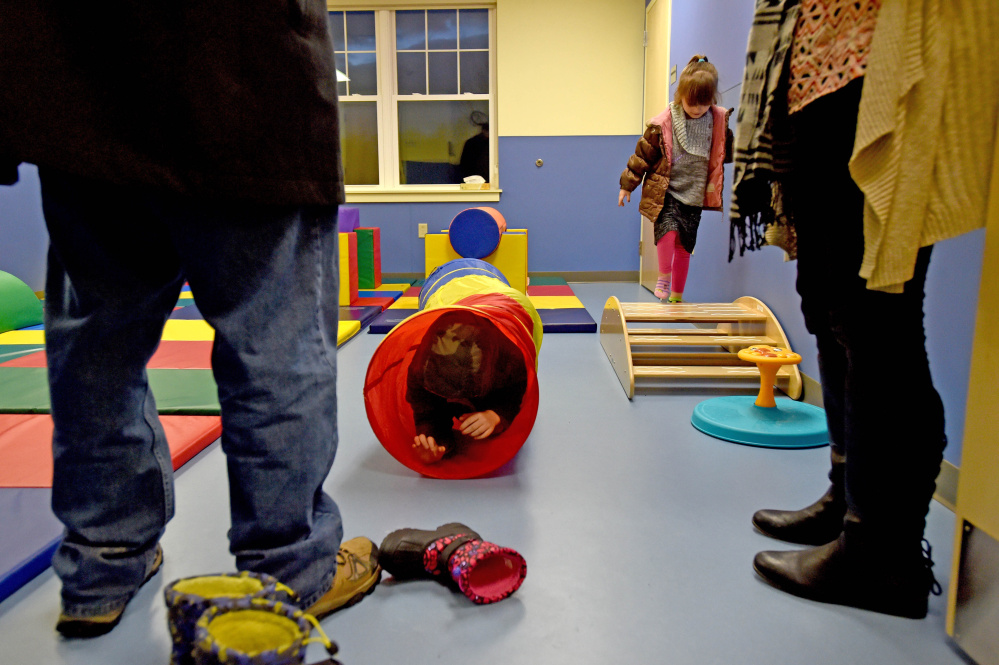 Scott Weston, 7, crawls through a rainbow wormhole as his sister Cecily, 4, right, takes the high road in the Gross Motor Room at a Woodfords Family Services preschool during school's the grand opening Thursday in Waterville.