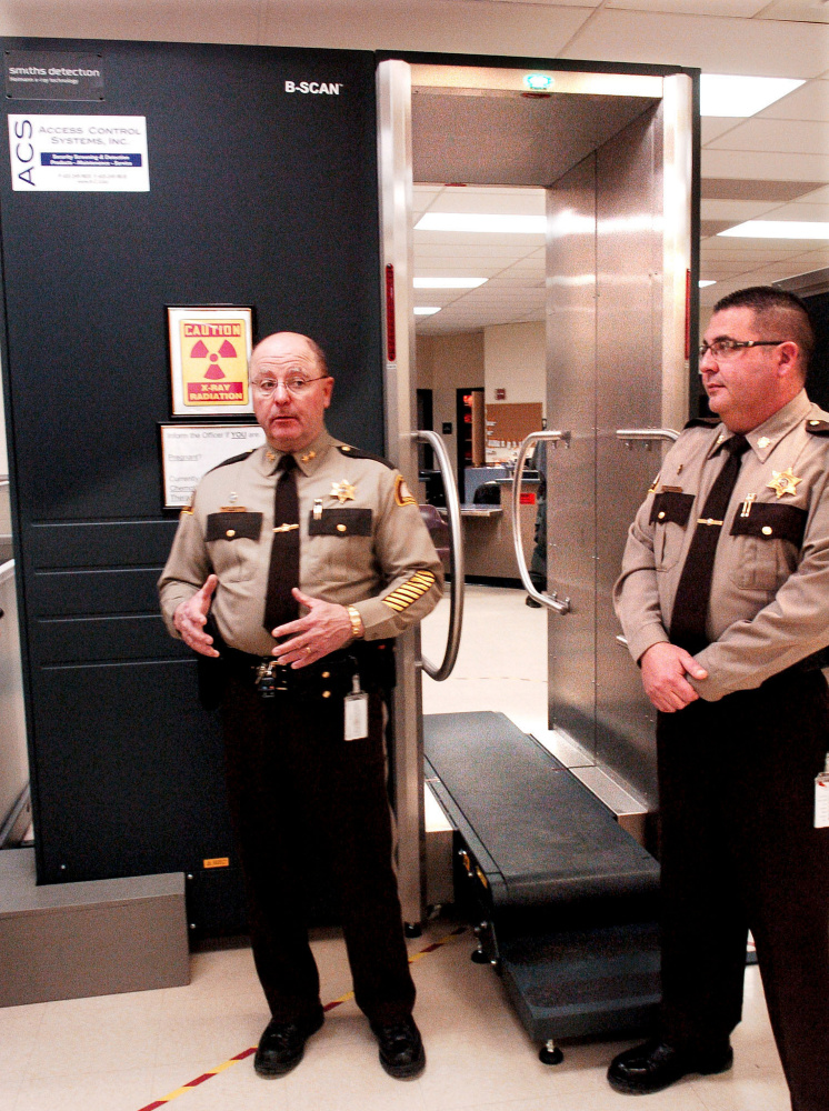 Somerset County Sheriff Dale Lancaster, left, and Somerset Jail Administrator Cory Swope discuss a new body scanner Thursday at the intake department at the East Madison jail. When an inmate gets on the conveyor belt, the scanner can detect objects that the inmate might be concealing inside his or her body in an effort to smuggle them into the jail.
