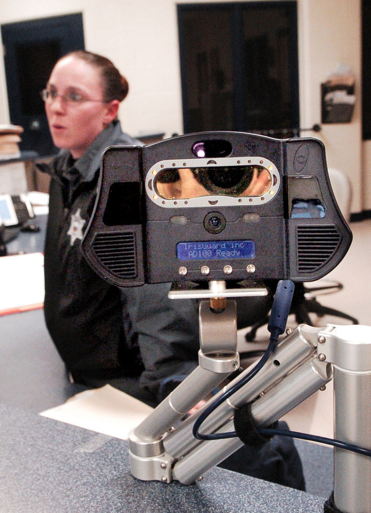 Somerset County Jail Corrections Officer Shannon Pooler talks about the iris scanner, foreground, that is used on inmates arriving at the intake section of the jail Thursday in East Madison. The iris scanner and a nearby body scanner are high-tech devices used to detect contraband and identify inmates.