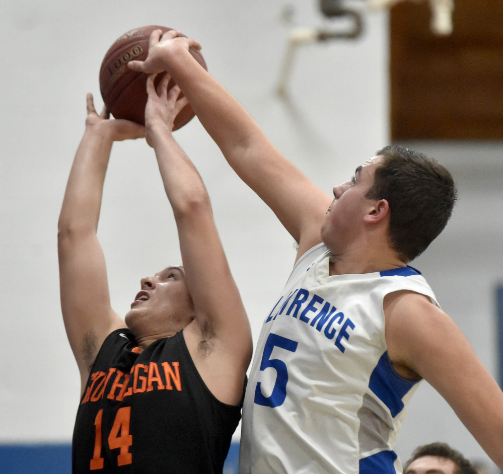 Lawrence junior Braden Ballard (5) rejects a shot by Skowhegan senior Joadel Mora during a Kennebec Valley Athletic Conference Class A game  Friday night in Fairfield.