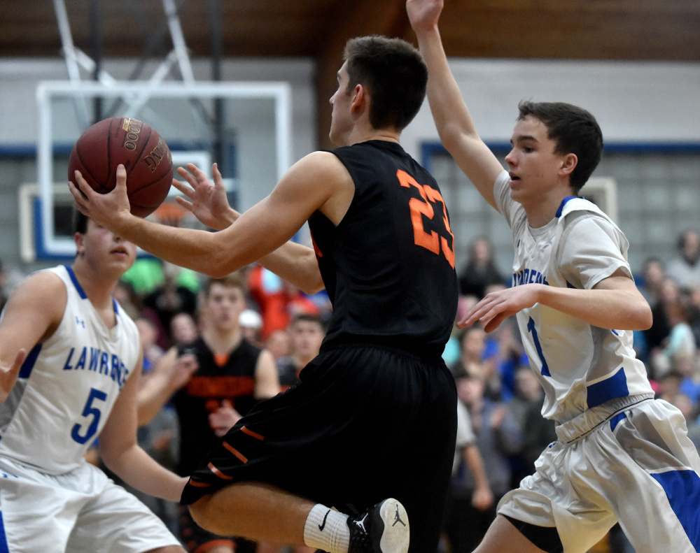 Skowhegan senior captain Brendan Curran, middle, drives to the hoop as Lawrence's Kobe Nadeau defends during a Kennebec Valley Athletic Conference Class A game  Friday night in Fairfield.