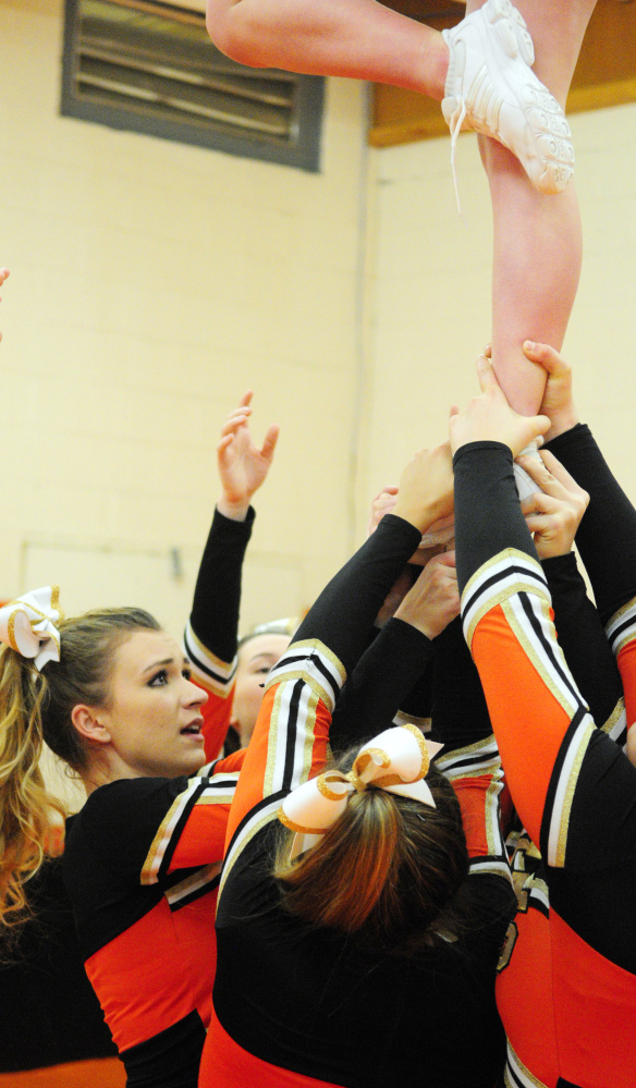 Sierra Goodridge, left, and her Tiger teammates practice a cheerleading routine Friday at Gardiner Area High School.