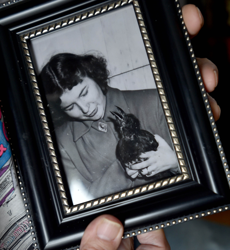 Lee Bureau holds a photo of his sister Joy and their pet crow, Smokey.