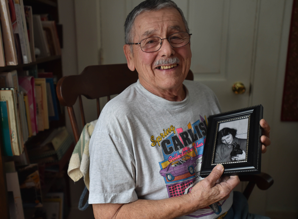 Lee Bureau poses for a portrait with a photo of his sister Joy and their pet crow, Smokey, at his home in Waterville on Friday. Smokey the crow, remembered as a smart and mischievous bird, died in 1952.