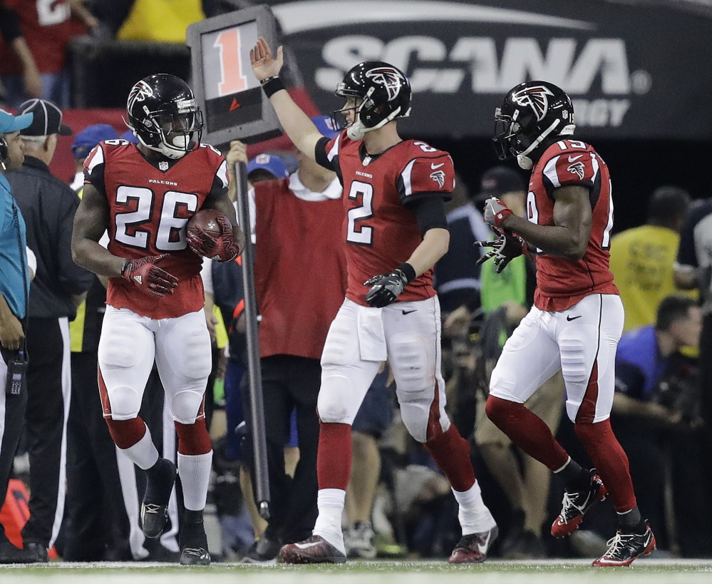 Atlanta quarterback Matt Ryan congratulates Tevin Coleman, left, after Coleman's touchdown run during the second half against Green Bay in the NFC championship game Sunday in Atlanta.