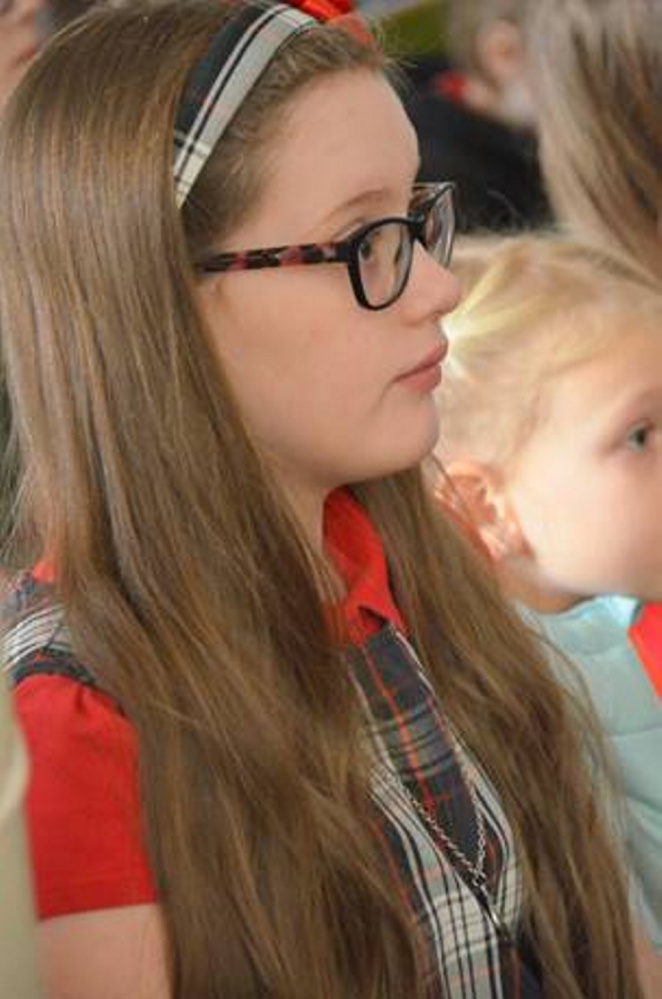 St. Michael School student Addison Burnham listens to Bishop Robert P. Deeley during his recent visit.