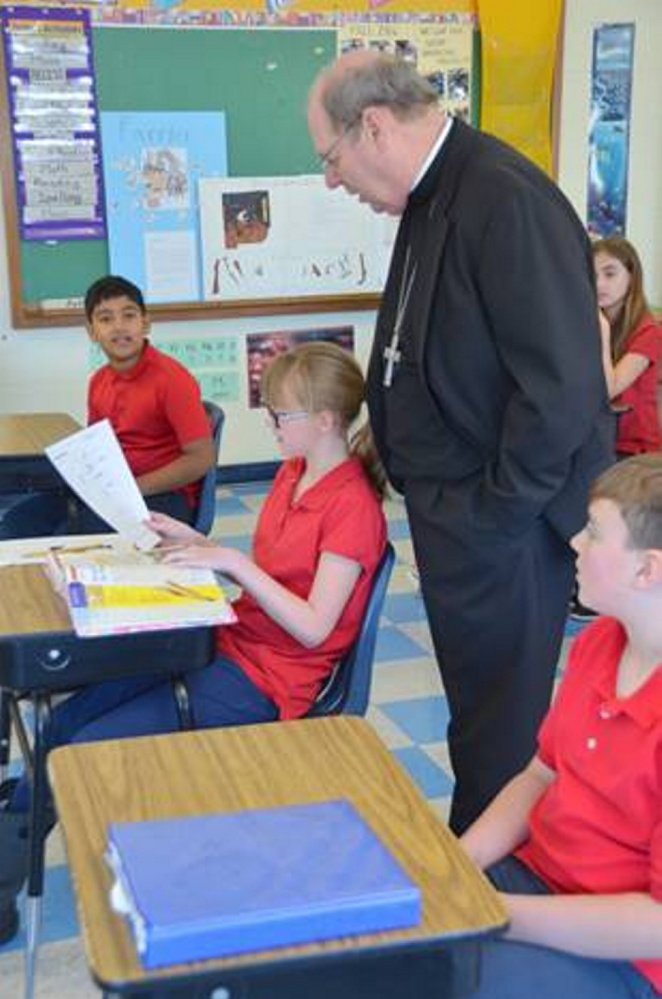Kya Douin shows Bishop Robert P. Deeley her work during a recent classroom visit.