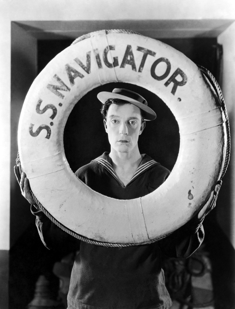 """Actor and director Buster Keaton wearing a sailor suit and holding a life preserver from the film, """"The Navigator,"""" directed by Keaton and Donald Crisp."""