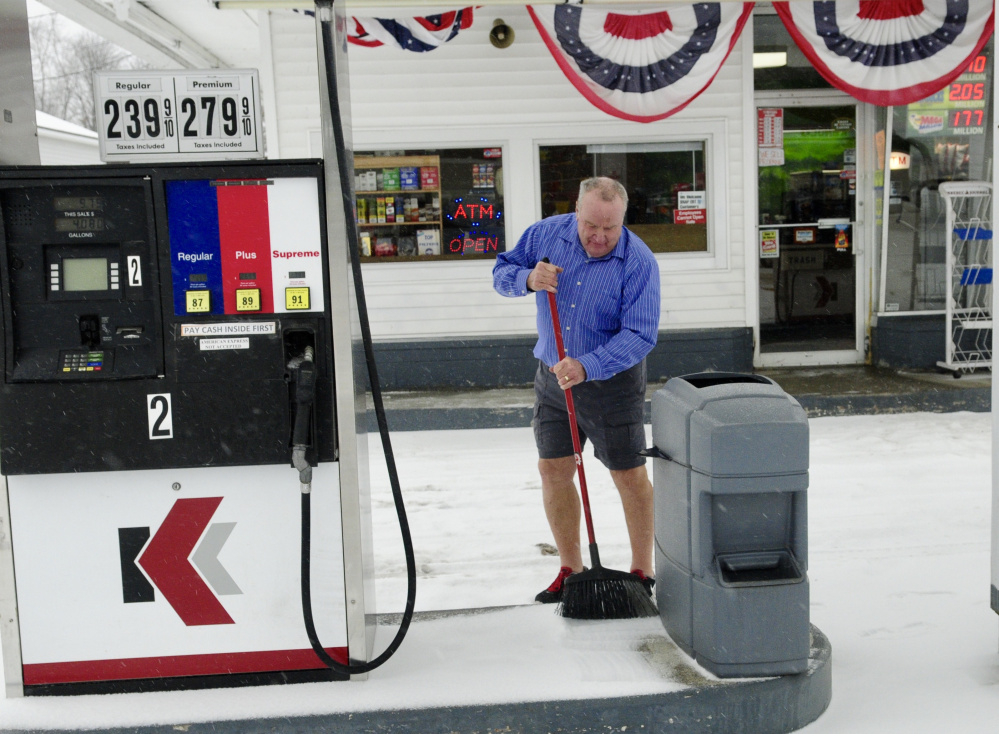 Bob Lippert sweeps snow from around the gas pumps at Easy Mart on State Street in Augusta on Tuesday.