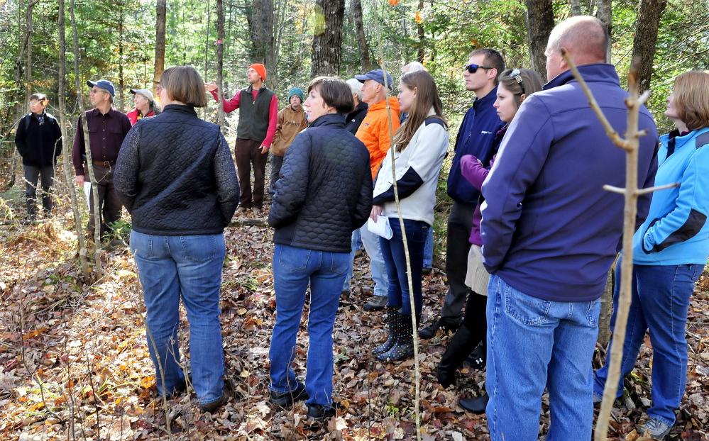Dylan Dillaway, center, chairman of the Sebasticook Regional Land Trust's Board of Directors, leads two dozen people through a marked trail during a dedication of Cob's Trail in the Kanokolus Bog Prerserve  in Unity on Oct. 19, 2014.
