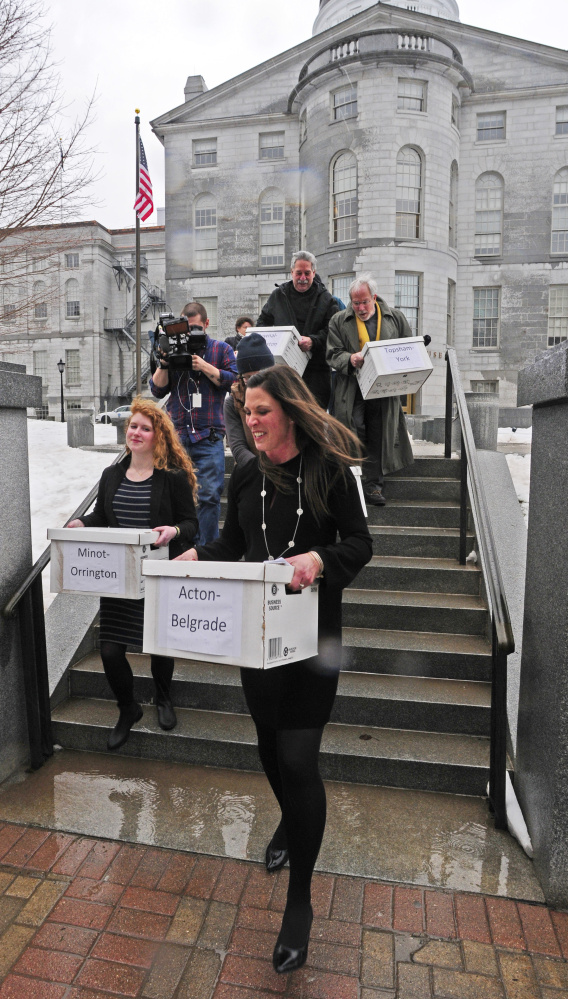 Supporters carry boxes of petition signatures Wednesday in Augusta from the Maine State House to the secretary of state's office in the Cross State Office Building.