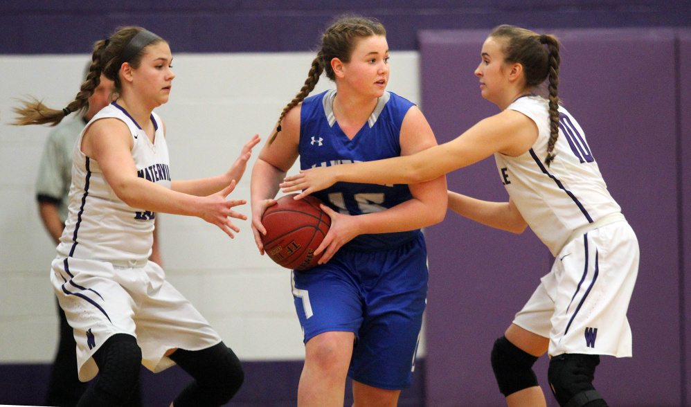 Lawrence's Hunter Mercier, center, tries to escape pressure by Waterville's Madeleine Martin, left, and Sophie Webb, right, during first-half action Wednesday in Waterville.