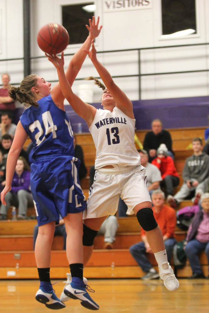 Waterville's Mackenzie St. Pierre, right, puts up a shot over the outstretched arm of Lawrence's Molly Folsom during first-half action Wednesday in Waterville.