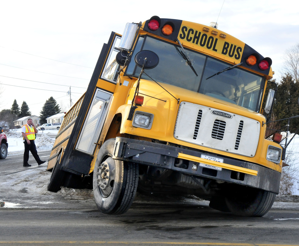 An investigator surveys the scene Thursday after a Winslow school bus ended up in a ditch and became stuck at the corner of Danielle and Benton avenues in Benton.