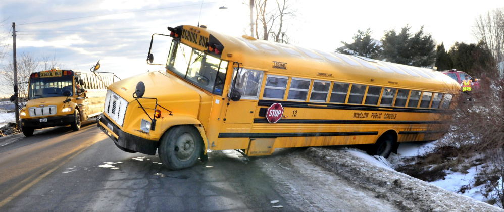 A school bus, at left, passes the scene where a Winslow school bus ended up in a ditch Thursday and became stuck at the corner of Danielle and Benton avenues in Benton. No injuries to the driver or the children on the bus were reported in the accident, which left one wheel of the bus in the air.