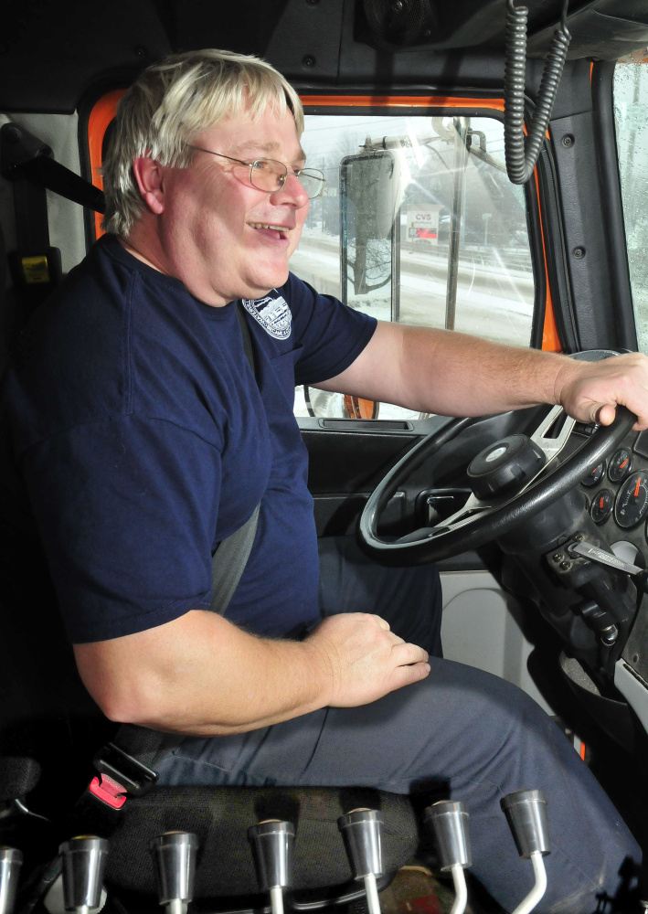 Waterville Public Works employee Dan Wilson sits next to various controls used to operate a department plow truck while clearing snow from the storm on Tuesday.