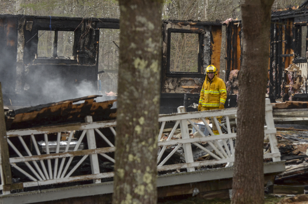 A firefighter walks among the smoldering ashes Jan. 23 at the scene of the fatal fire in the Knox County town of Washington.