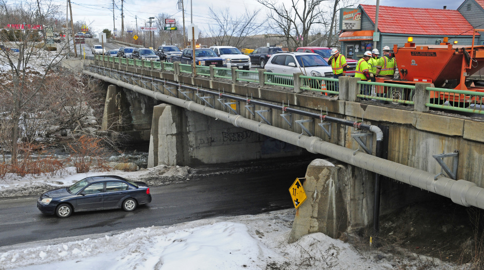 This Friday photo shows the Bridge Street Bridge over Cobbosseecontee Stream in Gardiner, where work is scheduled to take place in 2019. The Maine Department of Transportation workers, at right, were there filling in potholes.