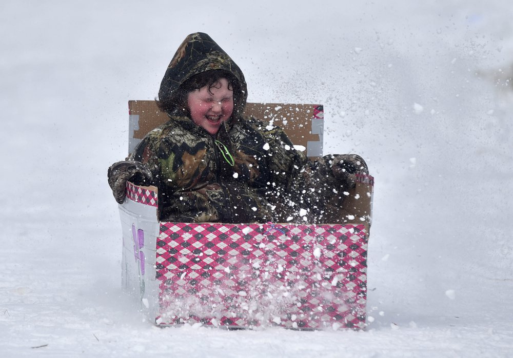 A competitor in the box sled races zips through a spray of snow last year at the annual winter carnival at Lake George Regional Park in Skowhegan. This year's annual carnival gets underway Saturday.