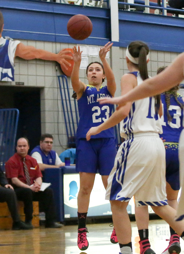 Mt. Abram's Summer Ross hits a 3-pointer in front of Madison defender Emily Edgerly during a game Tuesday night in Madison.