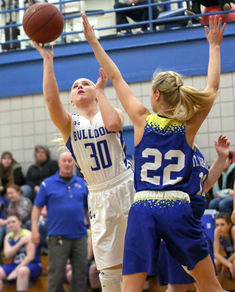 Madison's Madeline Wood, left, gets by Mt. Abram defenders Megan Sorel and Shania Campbell for a layup Tuesday.