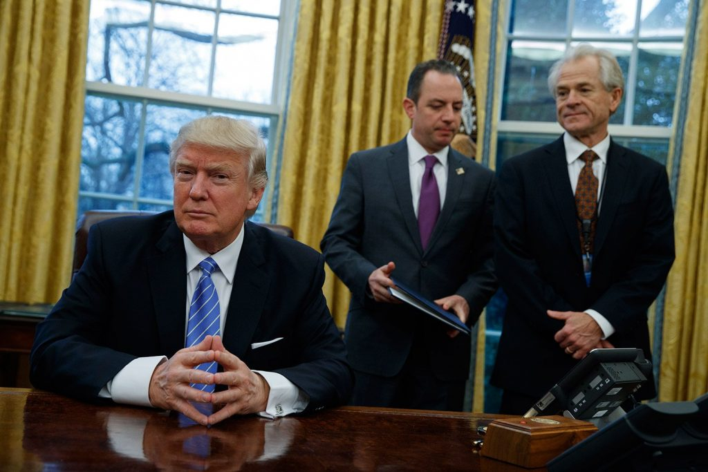 National Trade Council adviser Peter Navarro, right, and White House Chief of Staff Reince Priebus, center, wait for President Donald Trump to sign three executive orders Monday in the Oval Office.