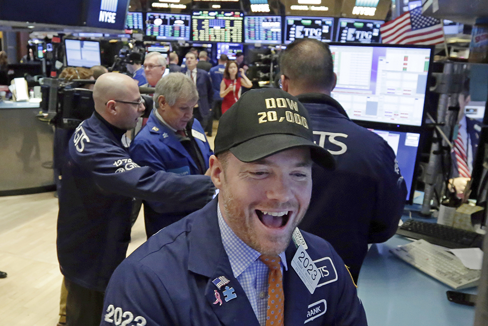 Specialist Frank Masiello wears a Dow 20,000 cap as he works on the floor of the New York Stock Exchange Wednesday.