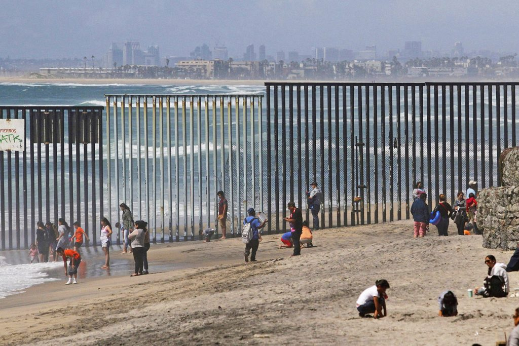 People are seen on the Mexican side of the U.S. border wall dividing a beach in Tijuana, Mexico, April 10, 2016.