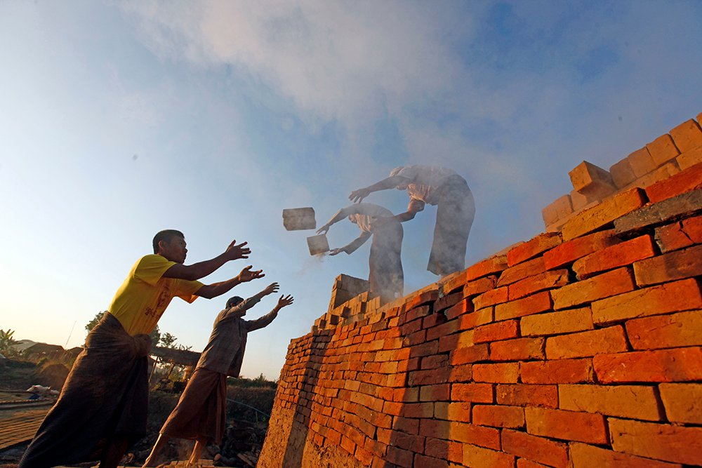 "Workers unload bricks at a brick-making factory in Naypyitaw, Myanmar.  ""It is obscene for so much wealth to be held in the hands of so few when 1 in 10 people survive on less than $2 a day,"" says Winnie Byanyima, executive director of Oxfam International. ""Inequality is trapping hundreds of millions in poverty; it is fracturing our societies and undermining democracy."""