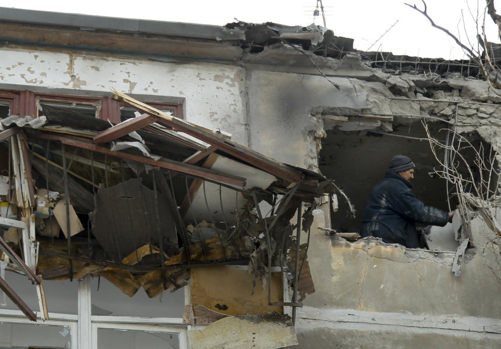 A municipal worker inspects damage to a home after shelling struck the city of Donetsk, eastern Ukraine, on Wednesday. At least 10 have been killed since Monday.