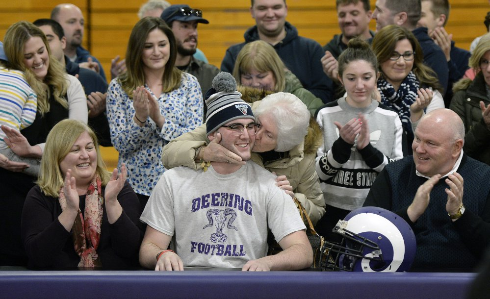 Raffaele Salamone of Deering High receives a kiss from his grandmother, Dianne Salamone, after signing a letter of intent Wednesday to play football at the University of Maine. Salamone's mother, Anne Salamone, left, and his father, Vinnie, applaud the signing.