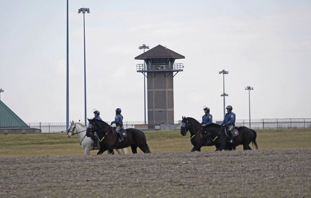 "Mounted police patrol travel along Smyrna Landing Road alongside James T. Vaugh Corrections center Thursday in Smyrna, Del. Inmates used ""sharp instruments"" to assume control of the building Wednesday, taking three prison guards and a woman counselor hostage."