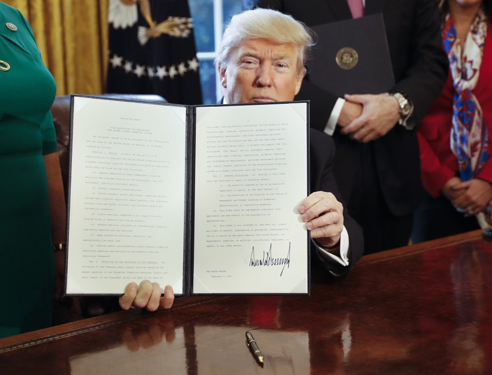 President Trump holds up an executive order he signed in the Oval Office of the White House in Washington on Friday. The executive order directs the Treasury secretary to review the 2010 Dodd-Frank financial oversight law, which reshaped financial regulation after 2008-2009 crisis.